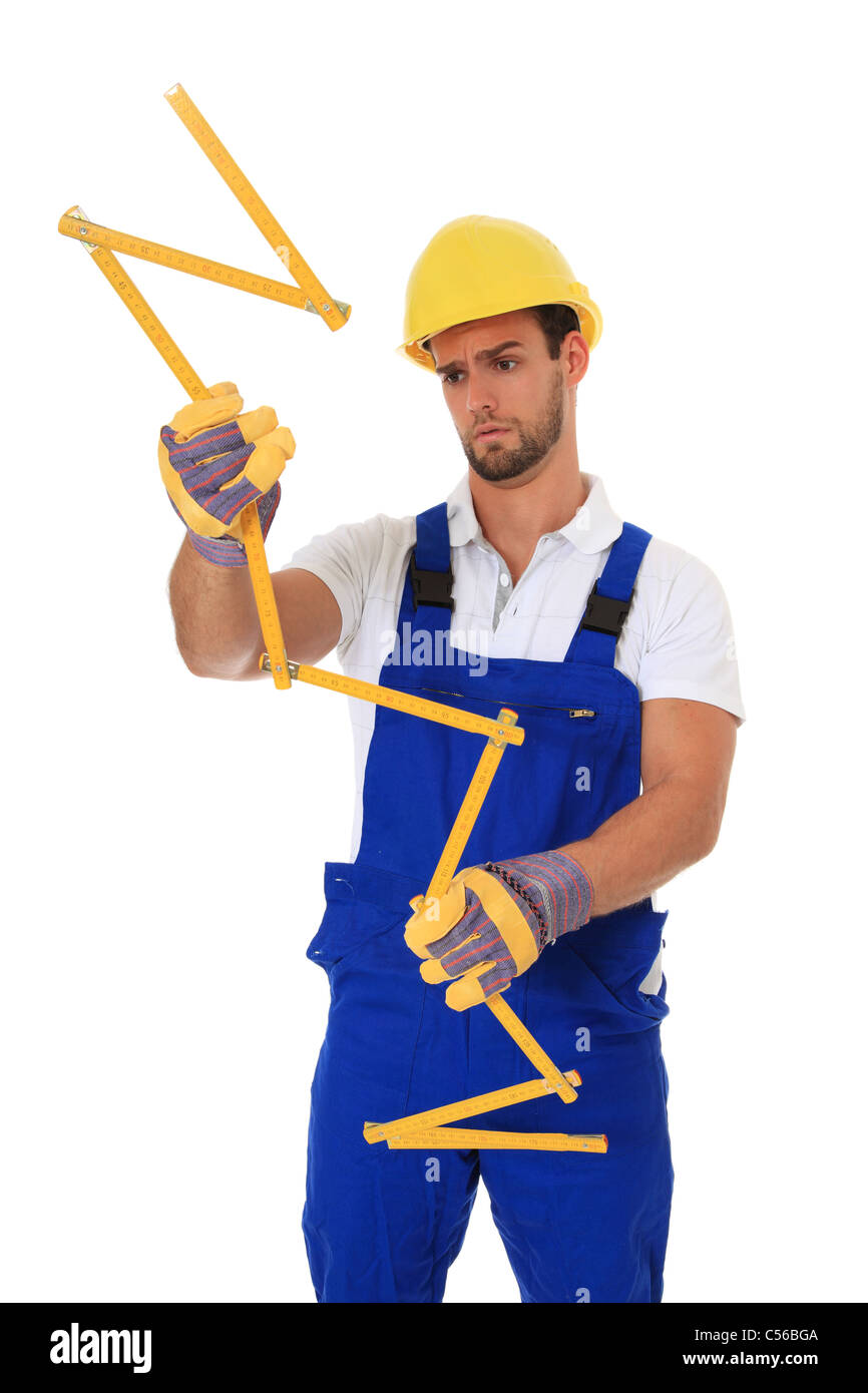 Clueless manual worker holding yardstick. All on white background. - Stock Image