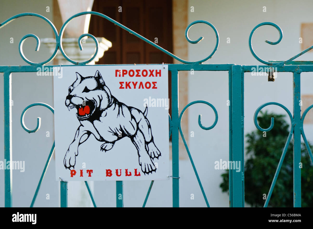 Beware of the pit bull dog sign in English and Greek - Stock Image