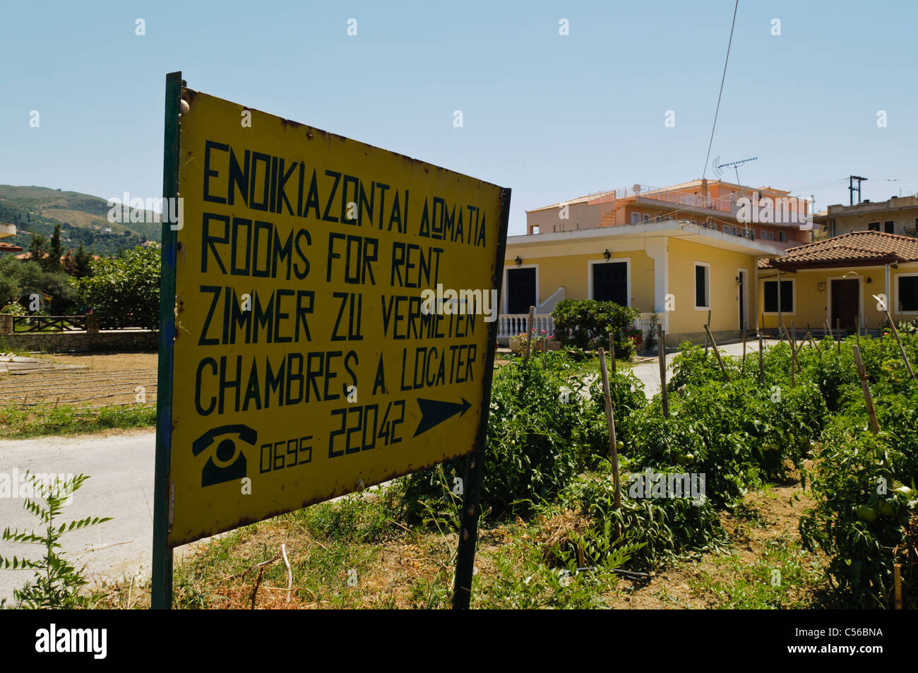 Multilingual sign advertising rooms for rent in Greek, English, German and French - Stock Image