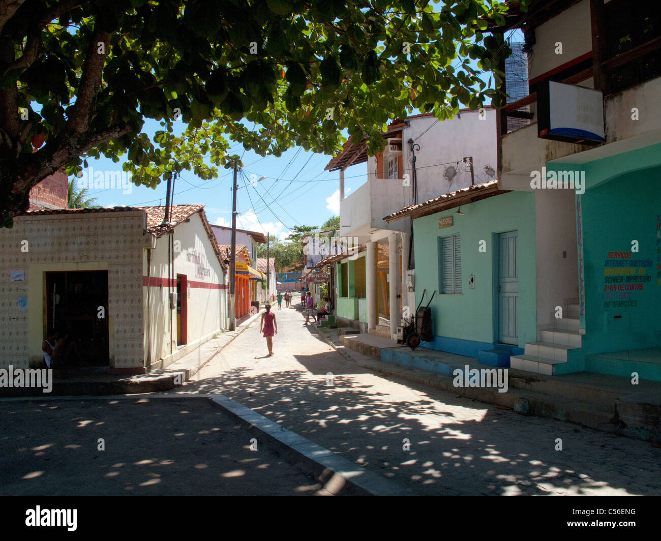 Girl walking down the street in the village of Velha Boipeba on Boipeba Island, Bahia State, Brazil - Stock Image