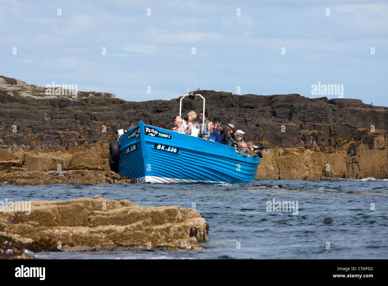 Farne Islands boat 'Glad Tidings II' with tourists on board close to rocks Stock Photo