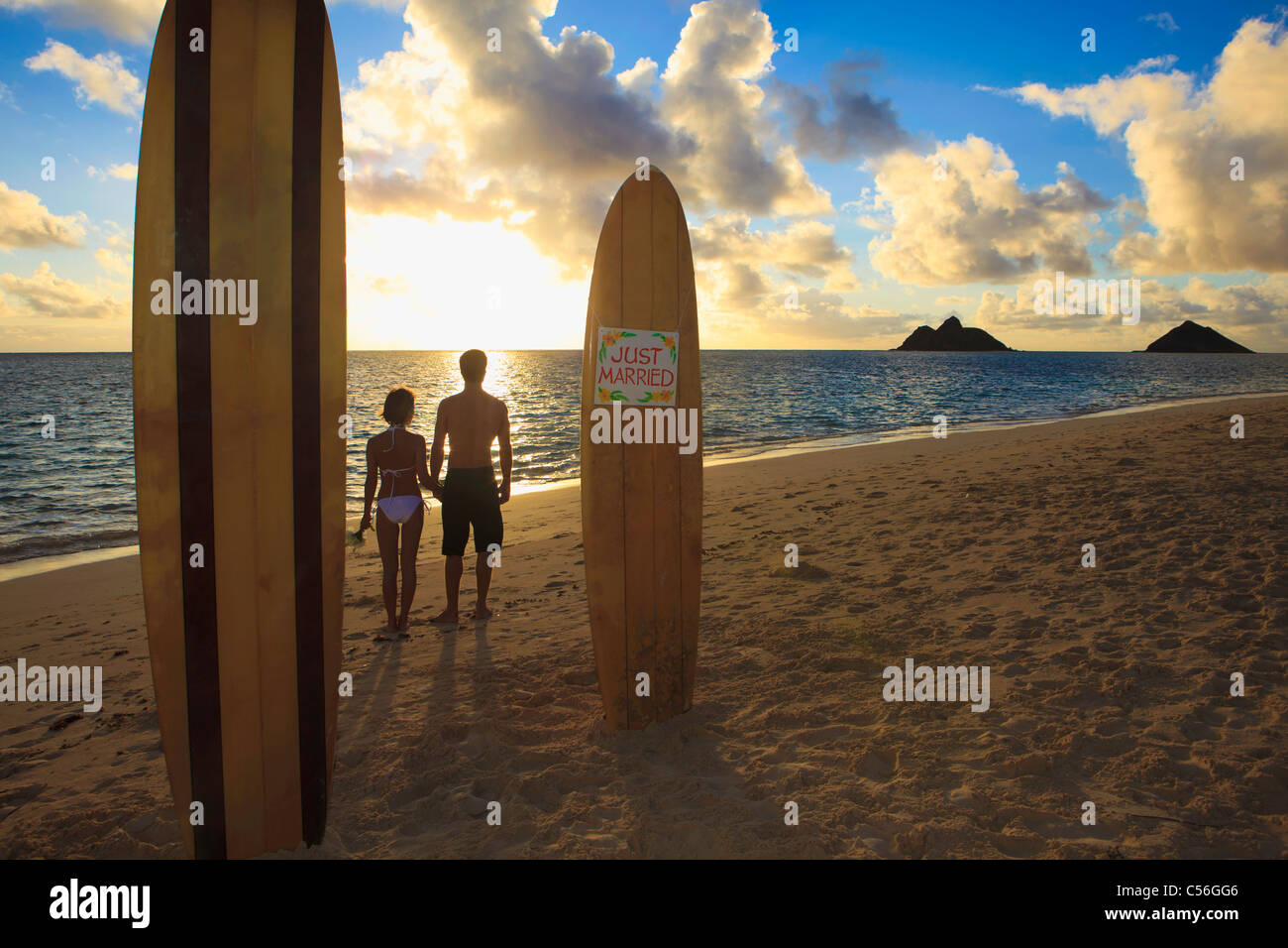newlywed couple on the beach with their surfboards at sunrise - Stock Image