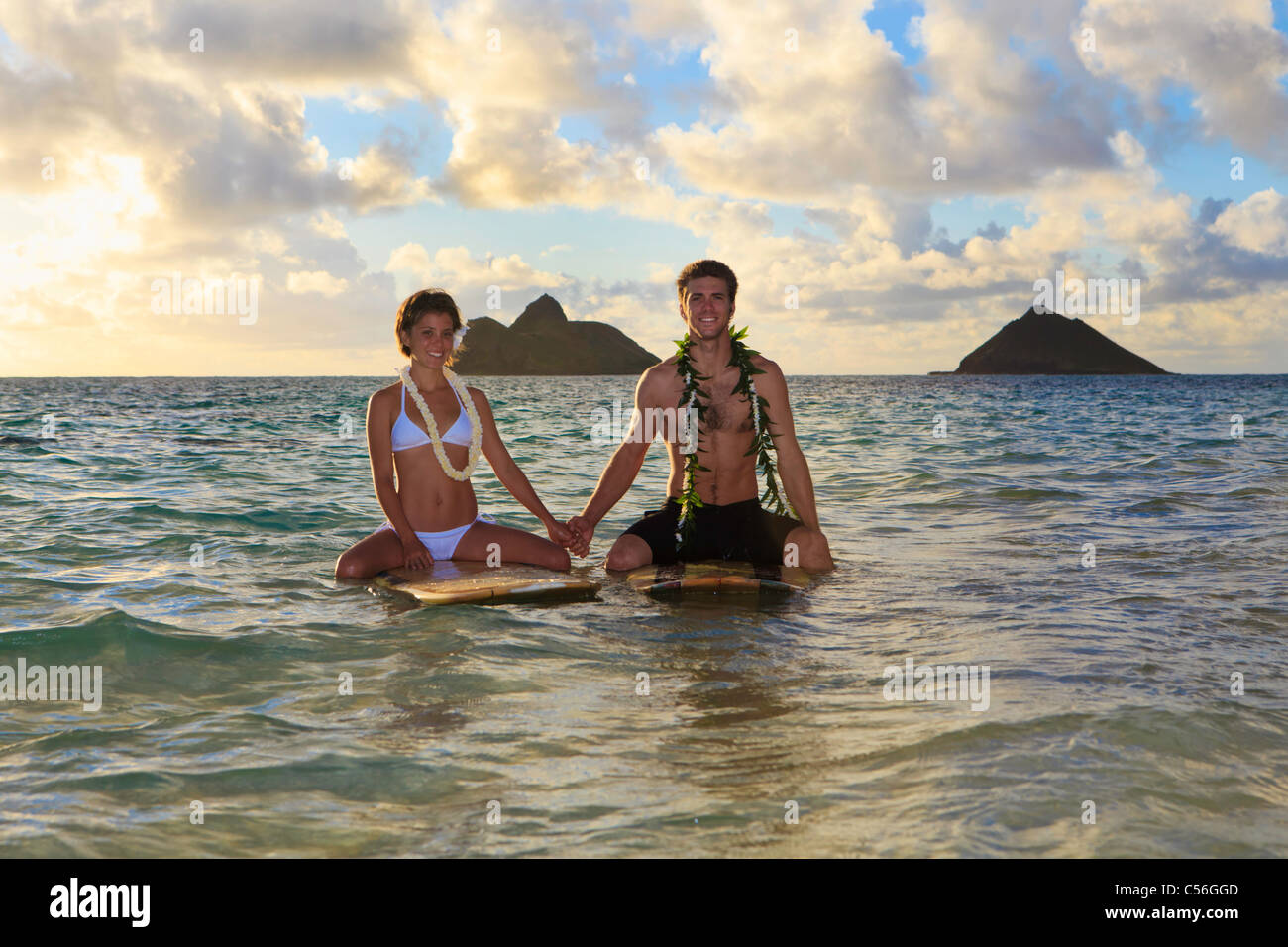 newlywed couple on their surfboards in hawaii - Stock Image