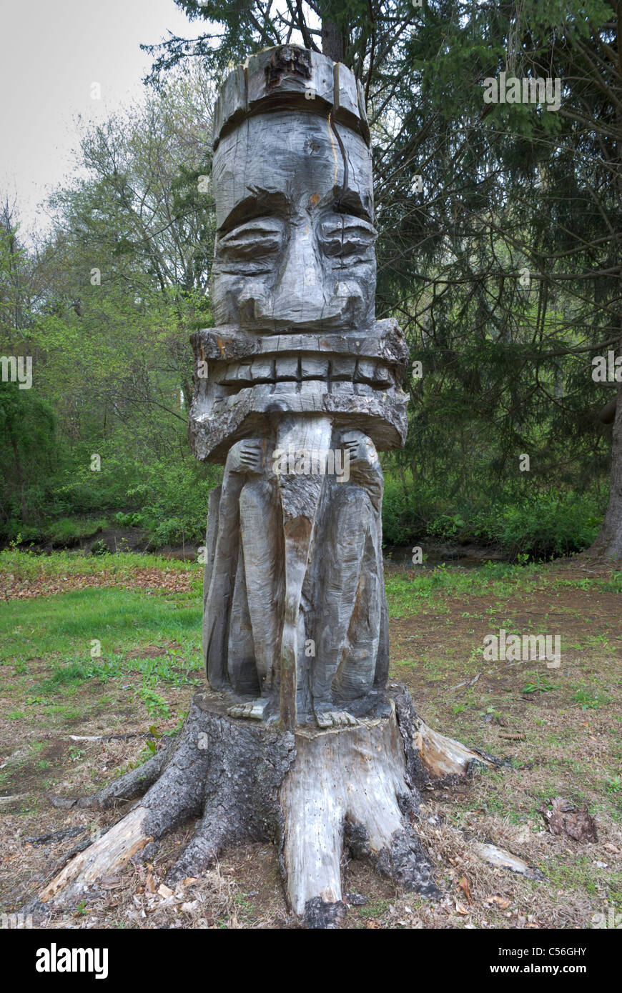 A creative wood carver has made an unusual totem from an old tree stump in Berkley, Massachusetts. - Stock Image
