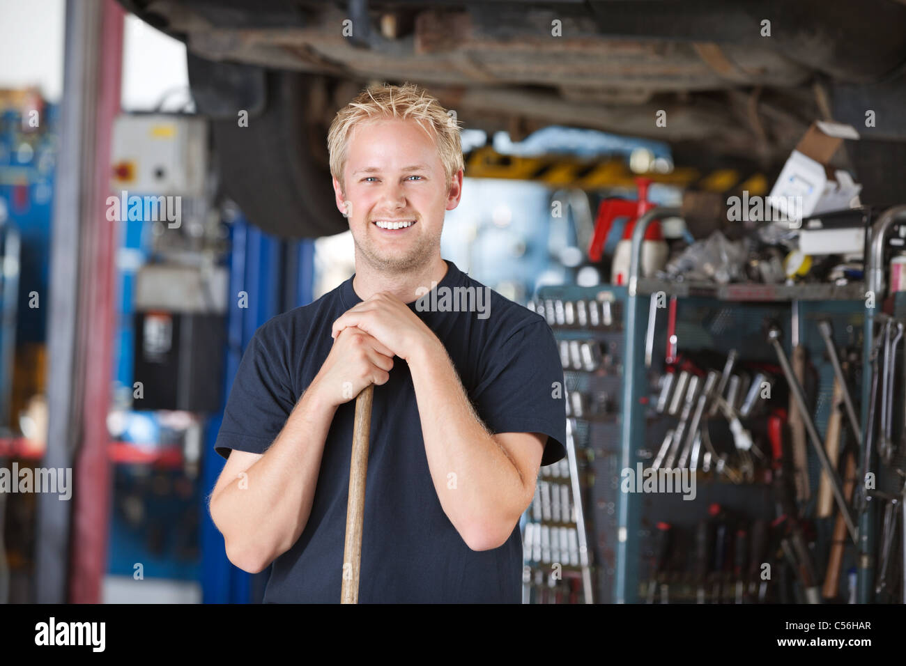 Portrait of smiling young mechanic leaning on a broom in a garage - Stock Image