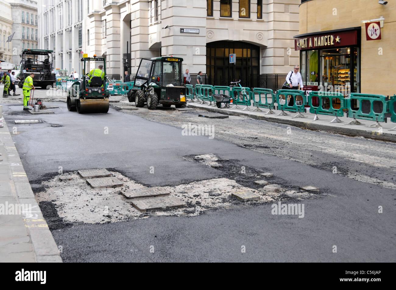 Street scene road works machines workmen & work in progress resurfacing worn out tarmac road in City of London - Stock Image
