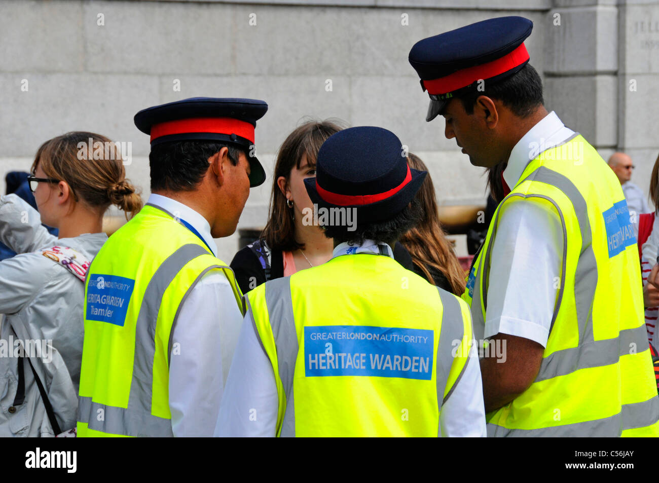 Three Heritage Wardens assisting visitors in London - Stock Image