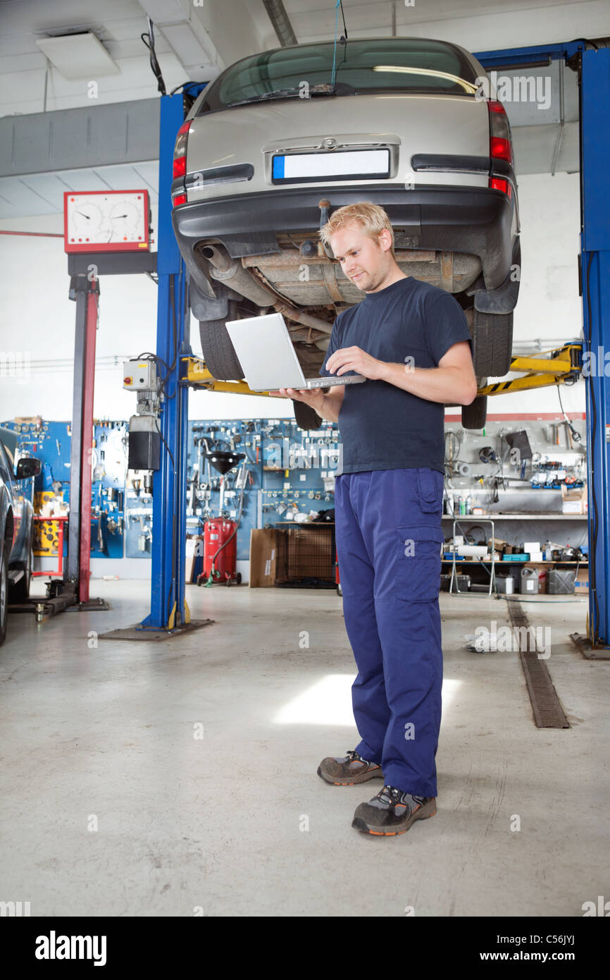 Full length portrait of young mechanic using laptop in his auto repair shop - Stock Image