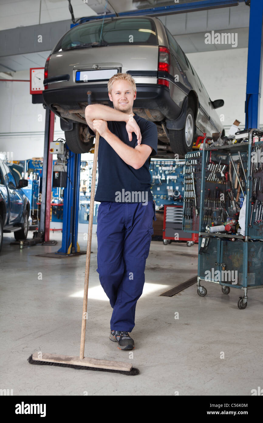 Full length portrait of young man leaning on broom in garage - Stock Image
