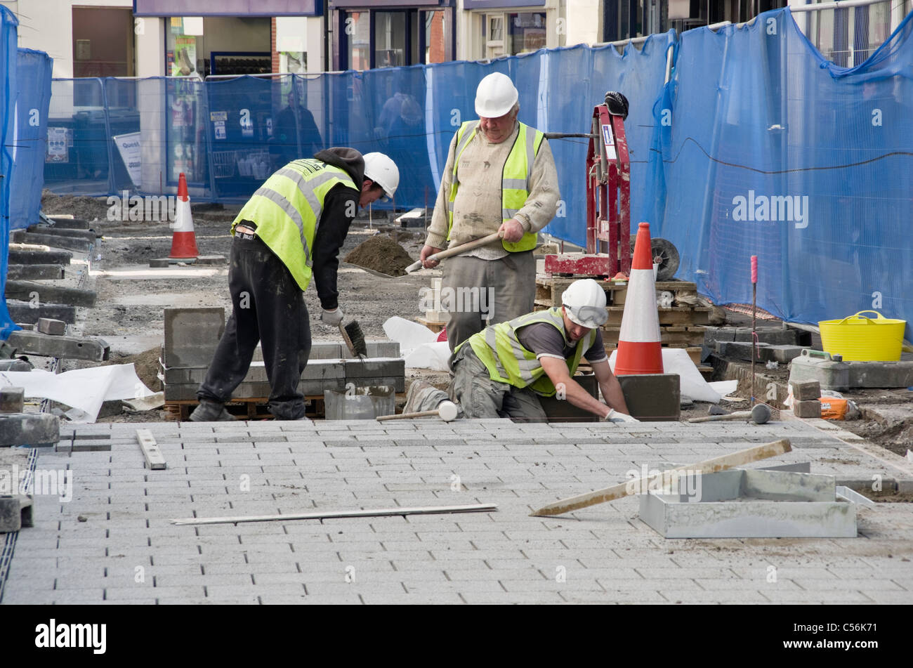 High Street, Bangor, Gwynedd, North Wales, UK. Council workmen digging up the road replacing paving stones in the - Stock Image