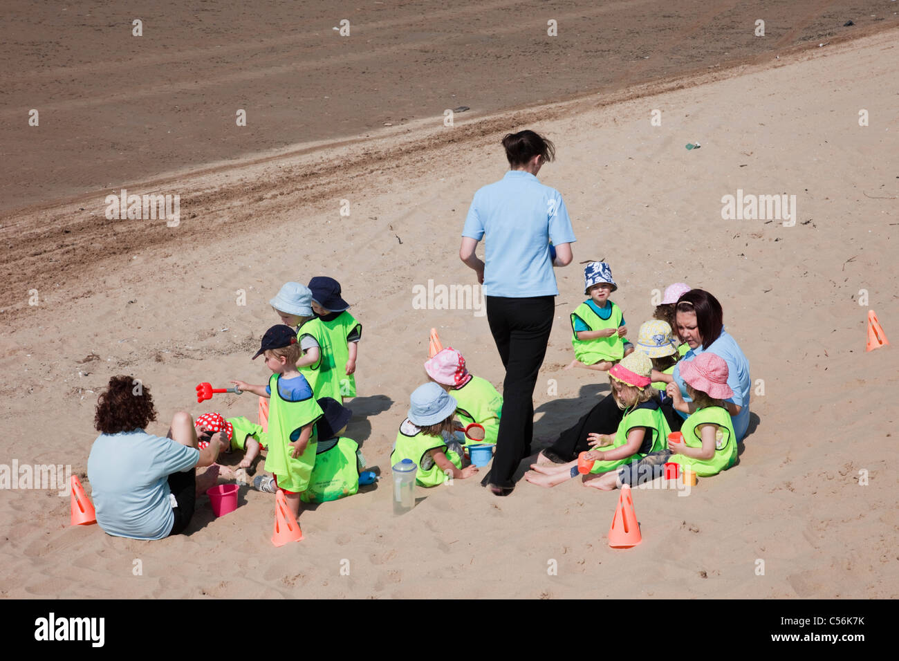 Group of nursery school children wearing hi-vis safety vests in a coned area on a trip to a sandy beach at the seaside - Stock Image