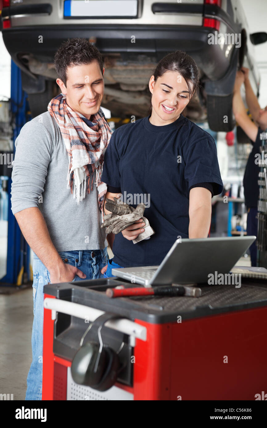 Female worker using laptop while standing next to client in garage with person in the background - Stock Image