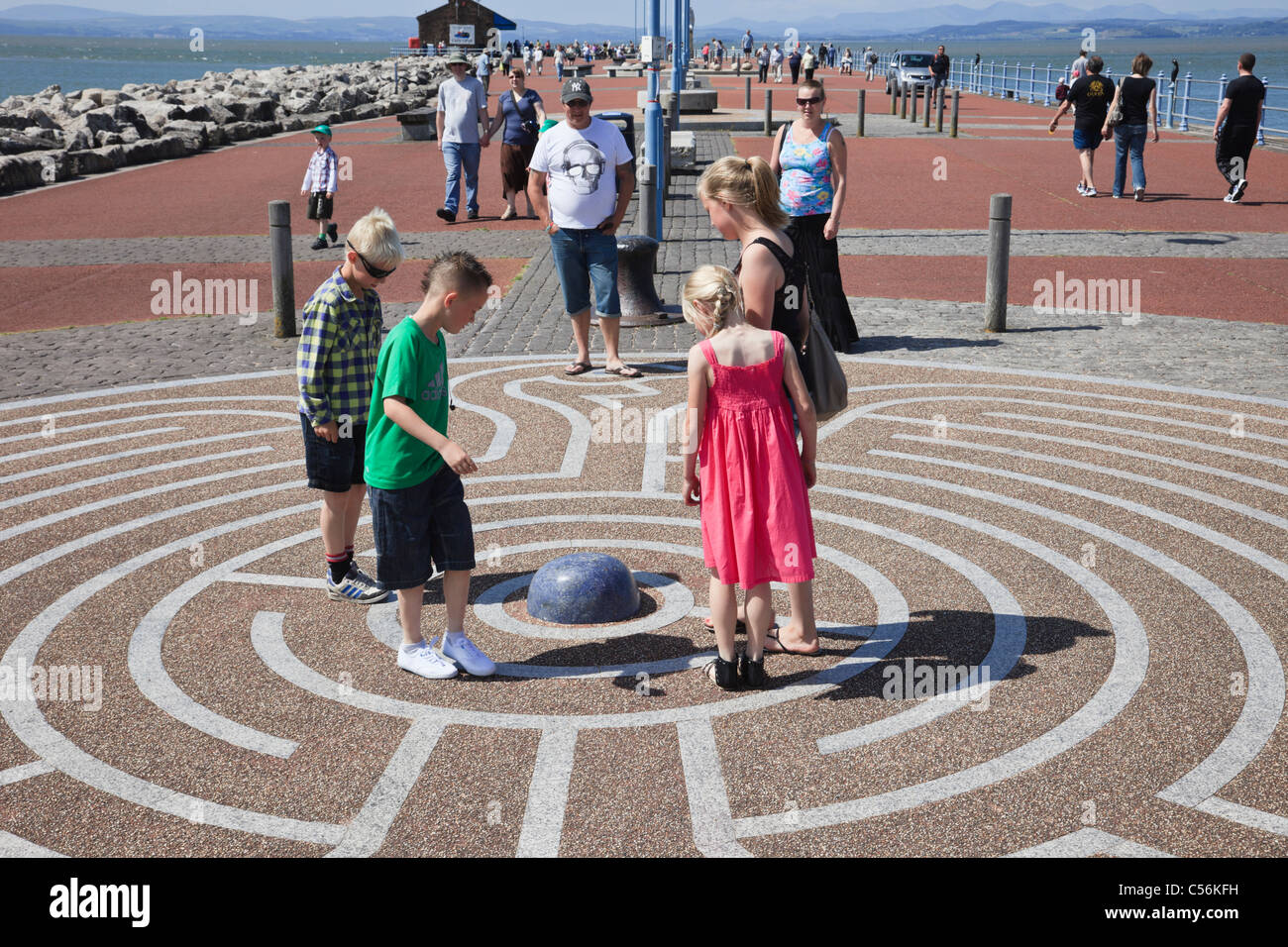 Morecambe, Lancashire, England, UK, Britain. Children walking around in the Tern Project maze puzzle on the stone - Stock Image