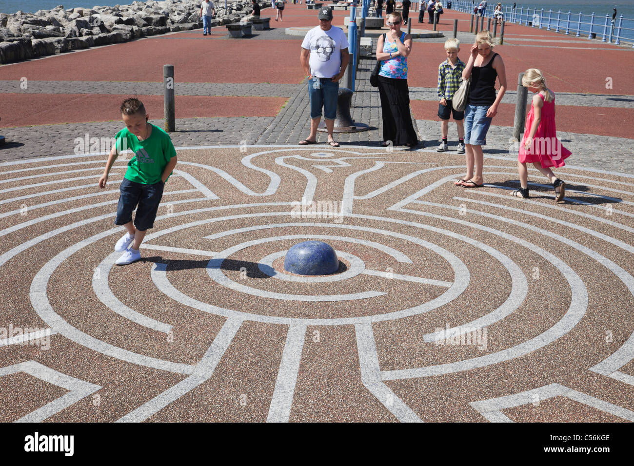 Morecambe, Lancashire, England, UK, Britain. Children playing in the Tern Project maze puzzle on the stone jetty - Stock Image