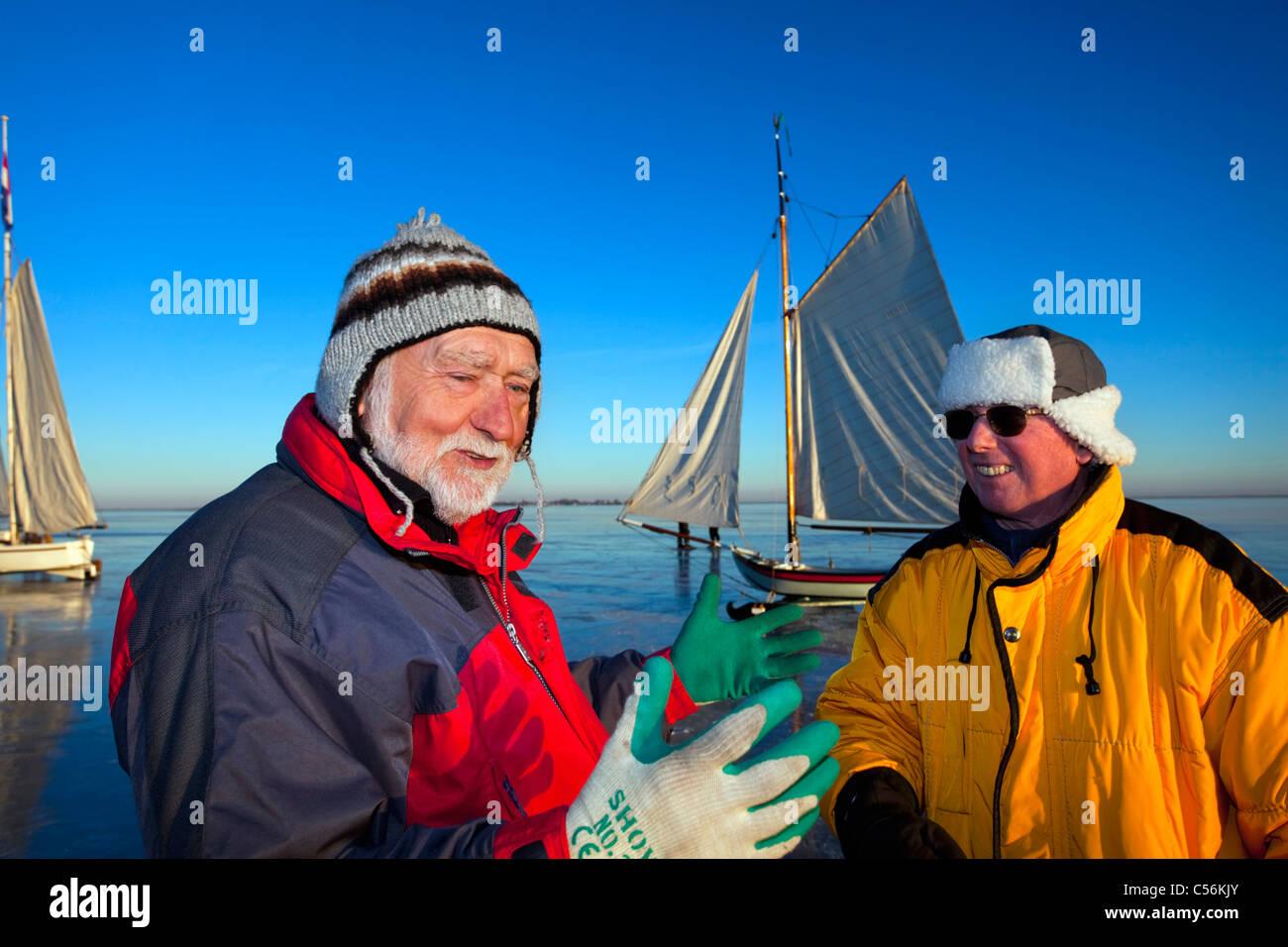 The Netherlands, Monnickendam. Ice sailing boats on frozen lake called Gouwzee. Captains talking. - Stock Image