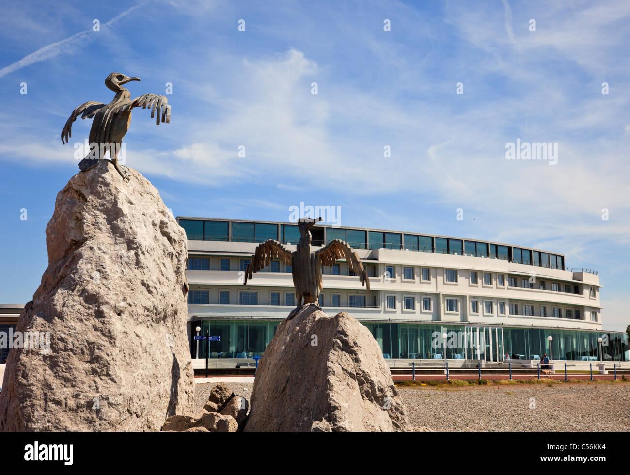 Cormorant steel sculptures and Art deco luxury Midland Hotel on the seafront. Morecambe, Lancashire, England, UK. - Stock Image