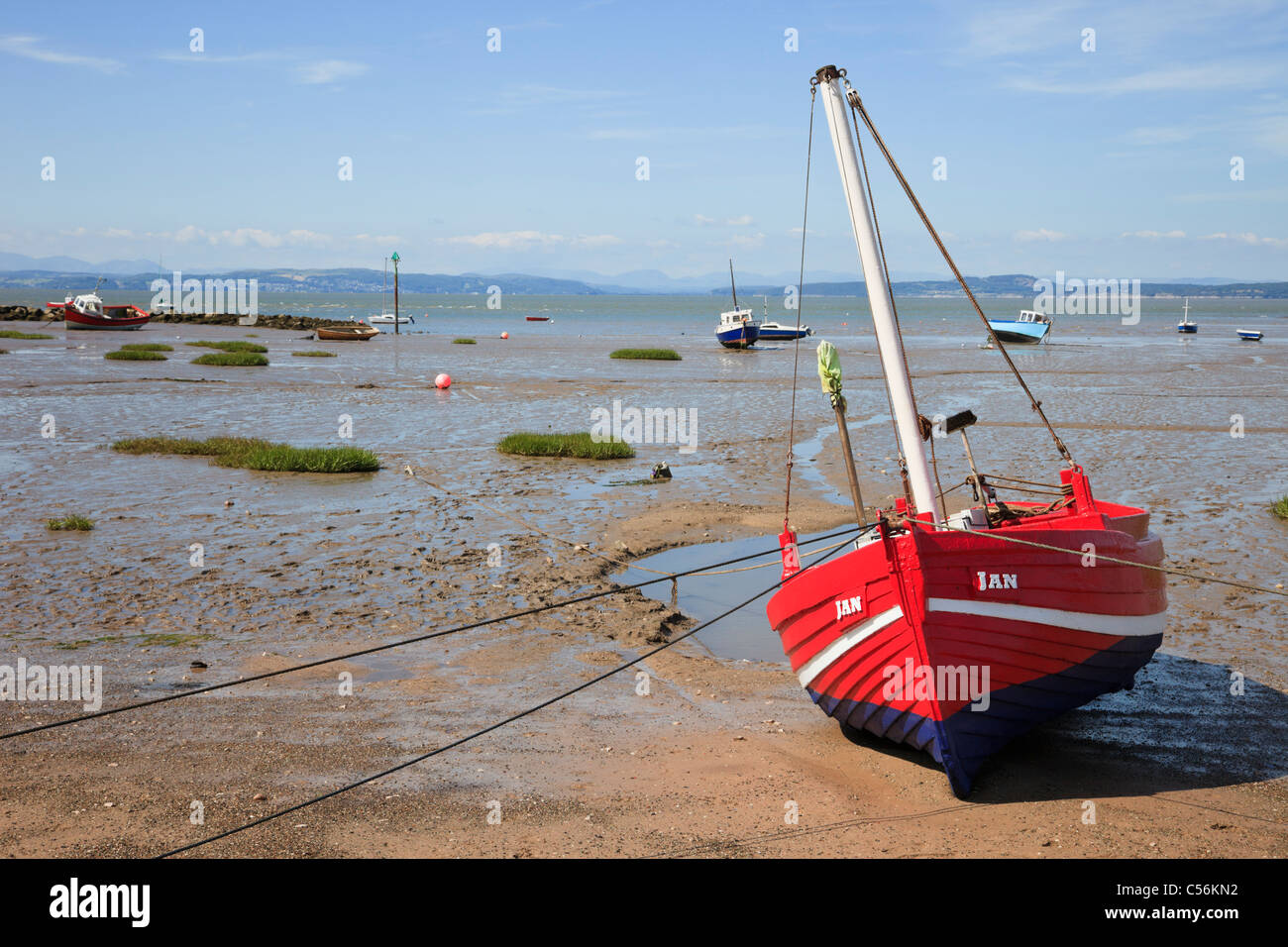 Beached red boat on the sands at low tide in Morecambe Bay, Lancashire, England, UK, Britain. - Stock Image