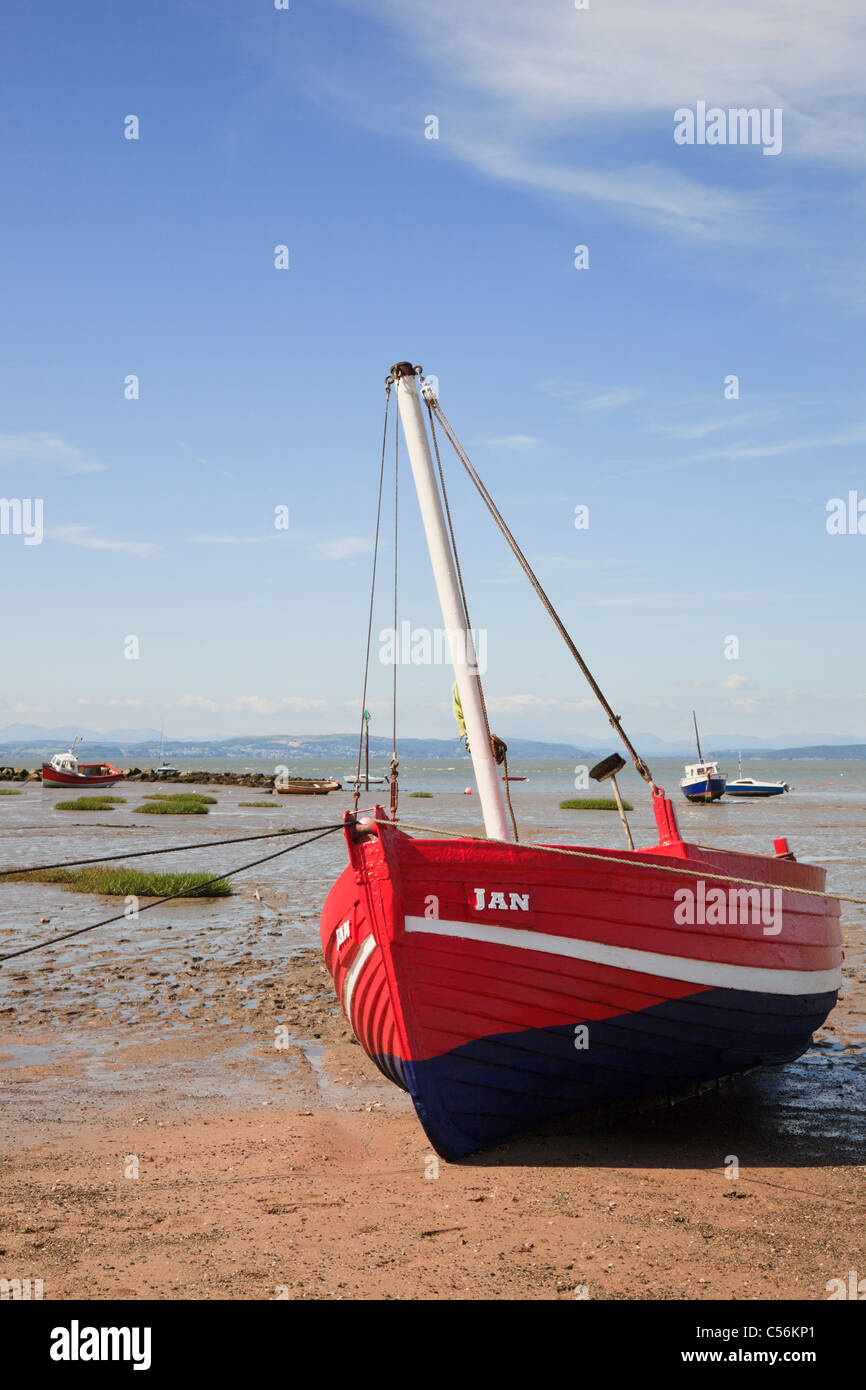 Beached red boat on Morecambe sands at low tide in Morecambe Bay, Lancashire, England, UK, Britain. - Stock Image