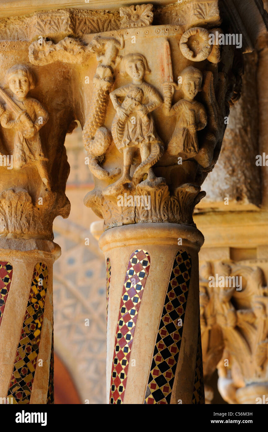 A pair of columns with richly guilded mosaic inserts topped with sculpted capitals in the cloister at Monreale - Stock Image