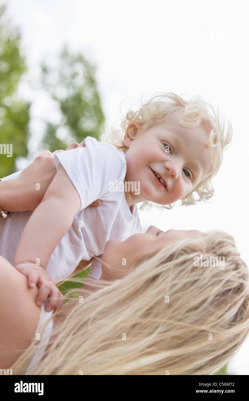 a64fd2a5da13 Portrait of baby boy playing with mother in park Stock Photo ...