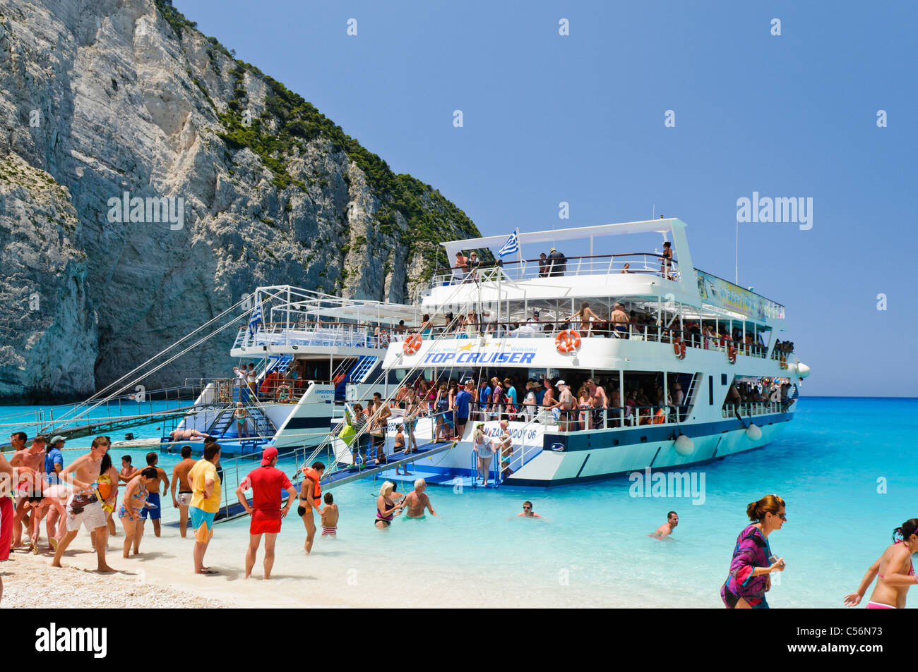 Tour boats anchored at a beach with very blue water - Stock Image