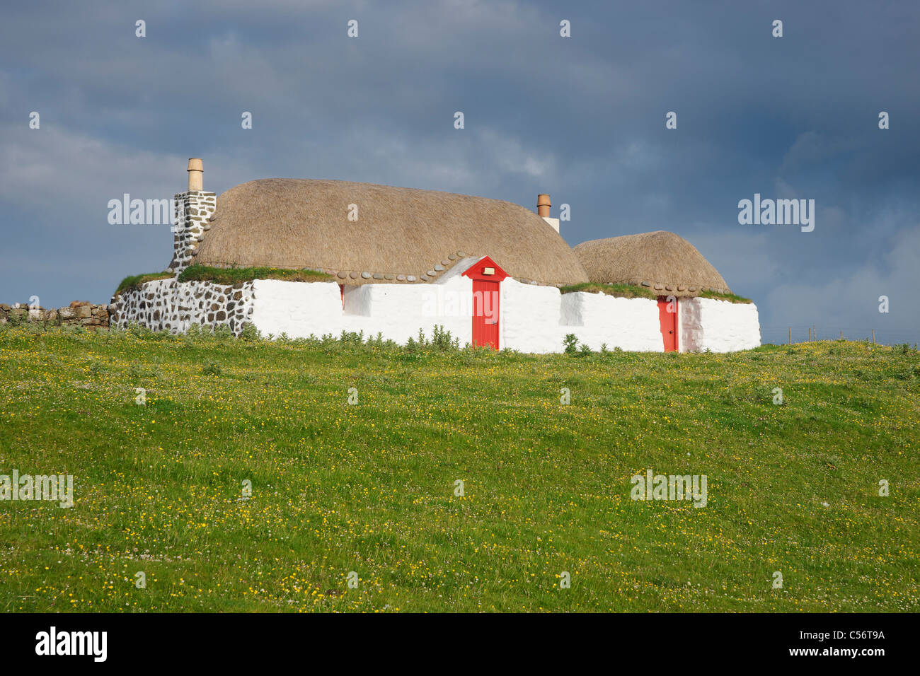 A white, thatched cottage with red door at Sraid Ruad, Tiree, Argyll, Scotland, UK. - Stock Image