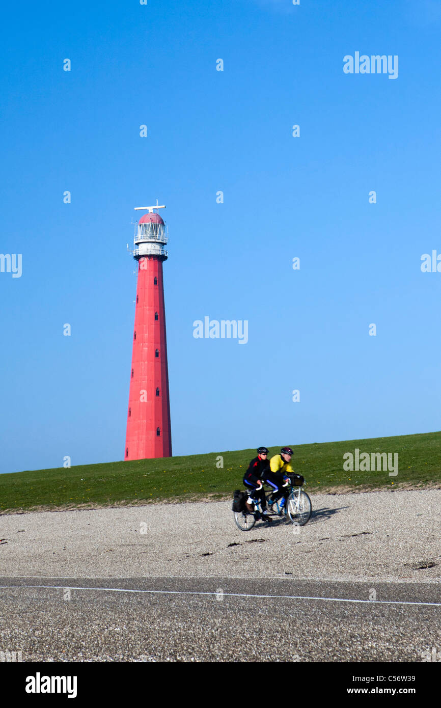 The Netherlands, Den Helder, lighthouse and cyclists, tandem. - Stock Image