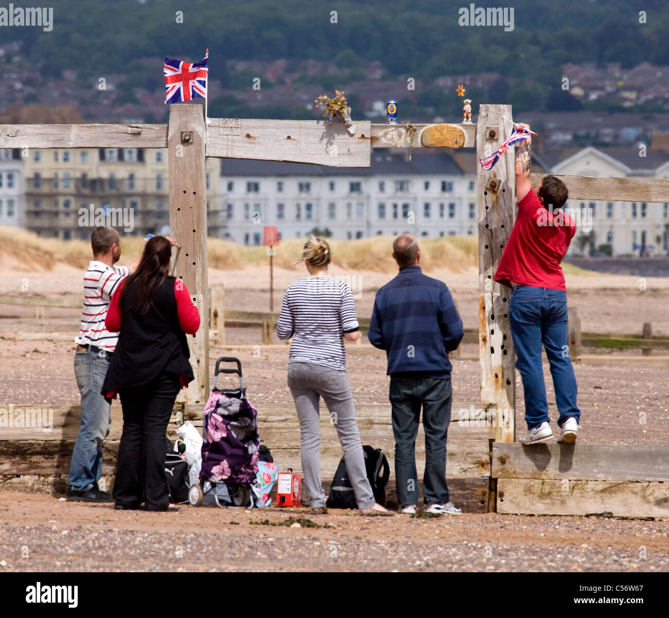 Family on a Devon beach decorating one of the local breakwaters - Stock Image