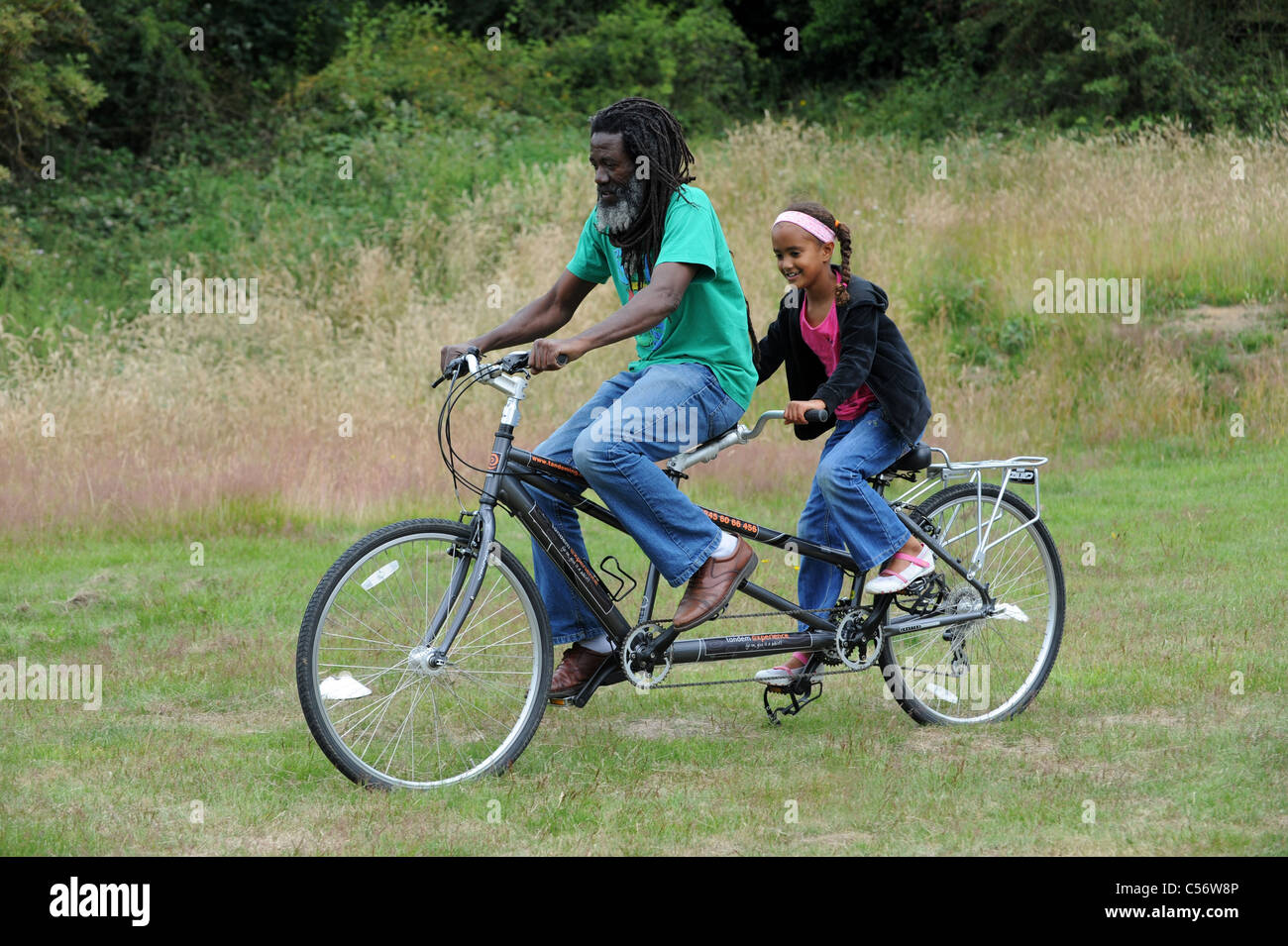 Man and girl riding a tandem bicycle in field Uk - Stock Image