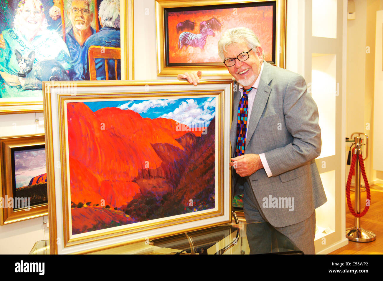 Artist and TV Presenter Rolf Harris holds a piece of his original art while smiling at camera Stock Photo