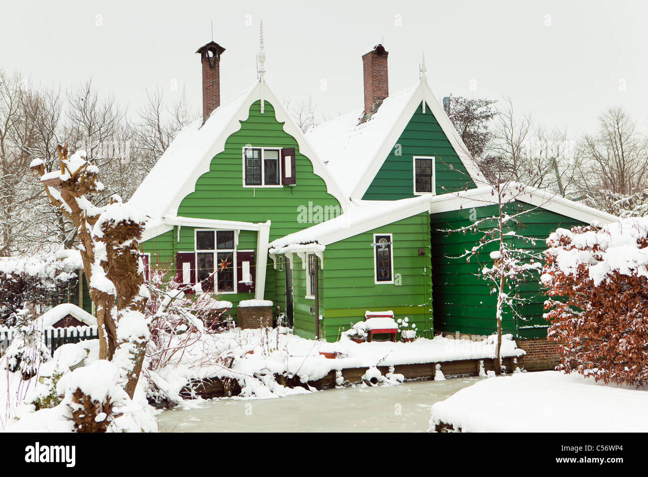 Zaanse Schans, village on the banks of the river Zaan with characteristic green wooden houses. Winter, snow. - Stock Image
