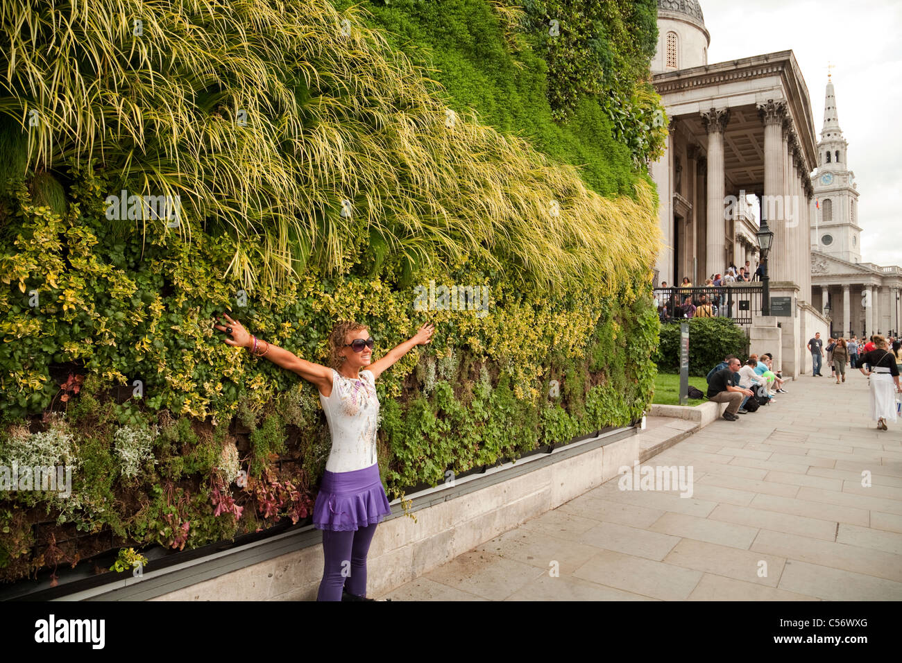 A tourist being photographed in front of  'A Living Masterpiece' - Trafalgar Square London UK - Stock Image