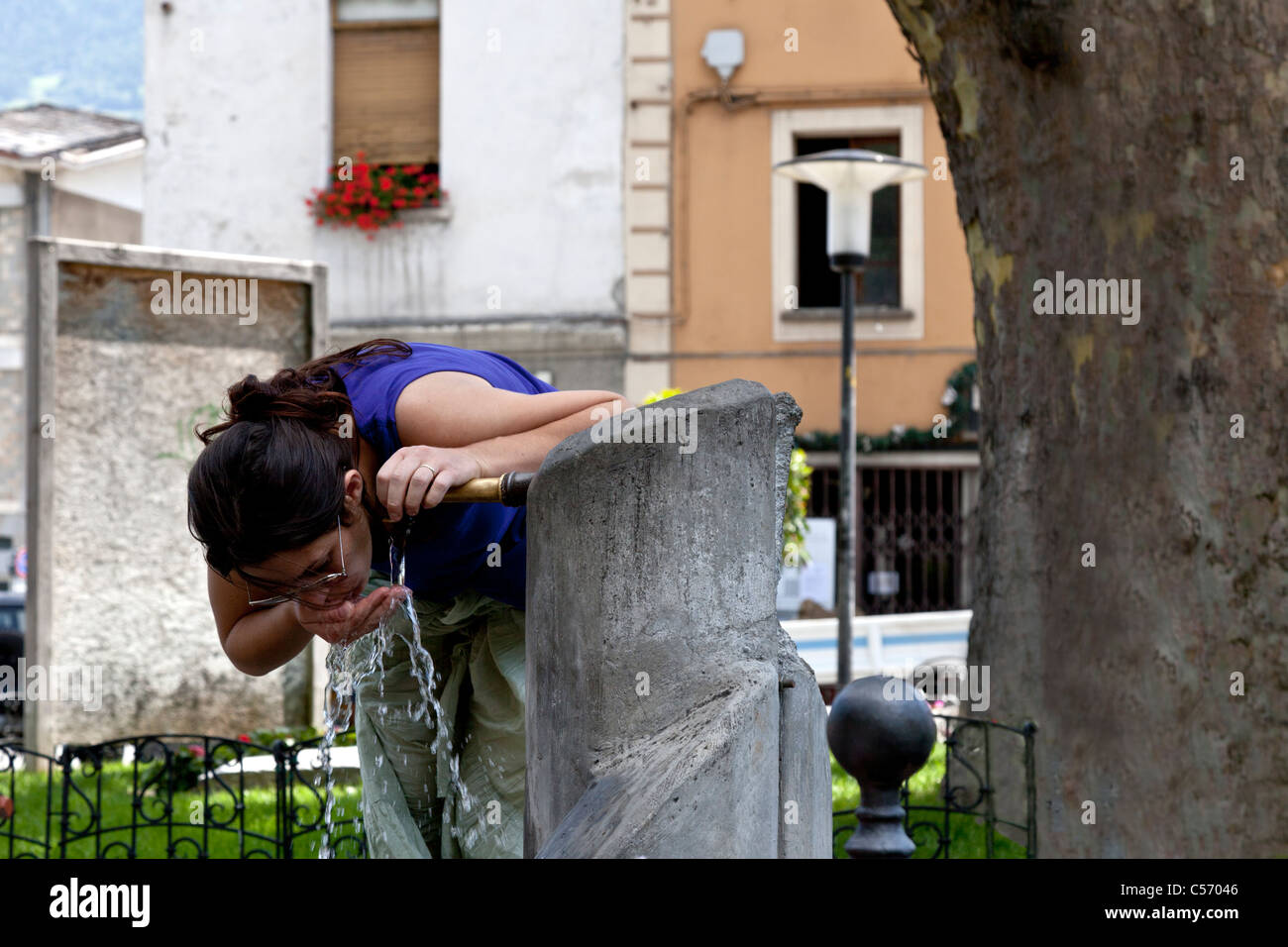 A young woman quenching her thirst at a fountain, in Aosta (Italy). Jeune femme étanchant sa soif à une - Stock Image