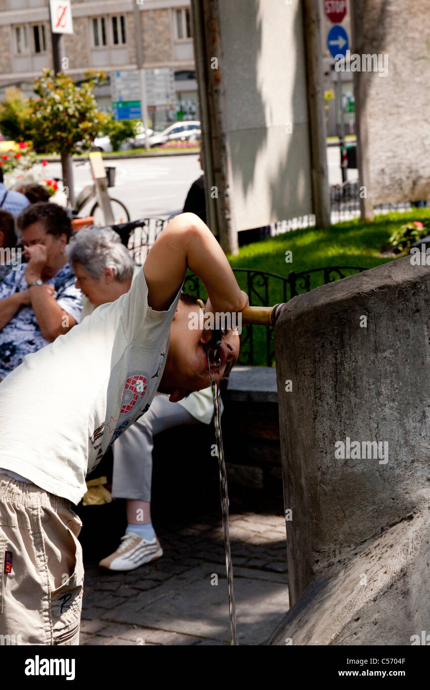 In Aosta, a young boy slaking his thirst at a fountain (Italy). Dans Aosta, jeune garçon étanchant sa - Stock Image