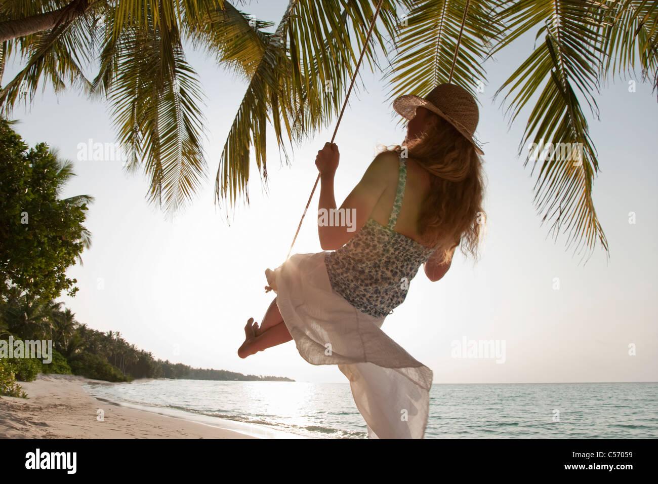 Woman swinging on tropical beach - Stock Image