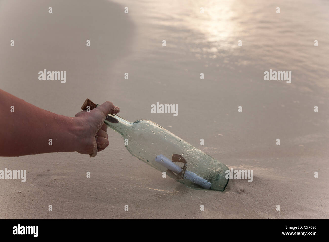 Person with message in a bottle at beach - Stock Image