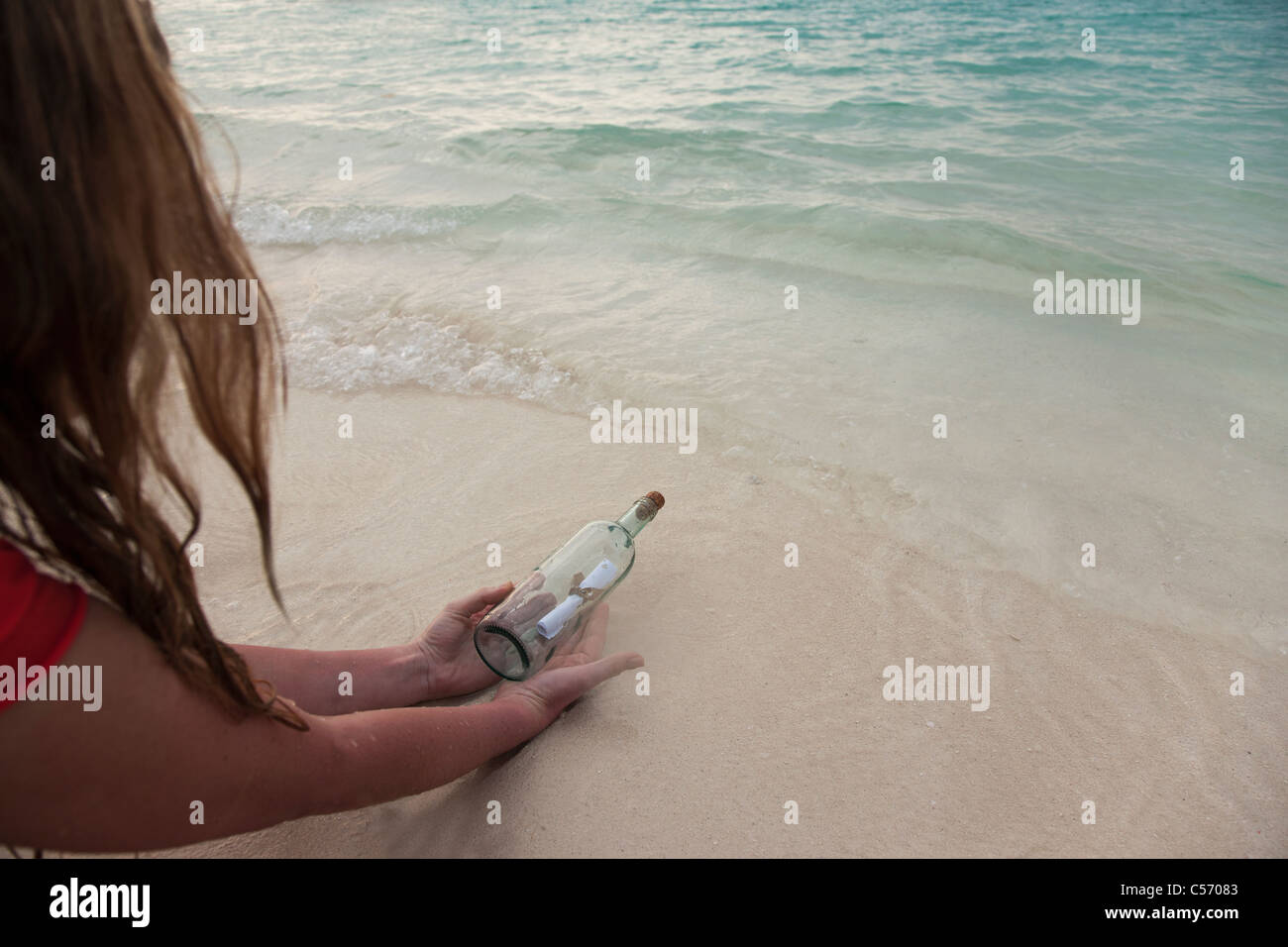 Woman with message in a bottle at beach - Stock Image
