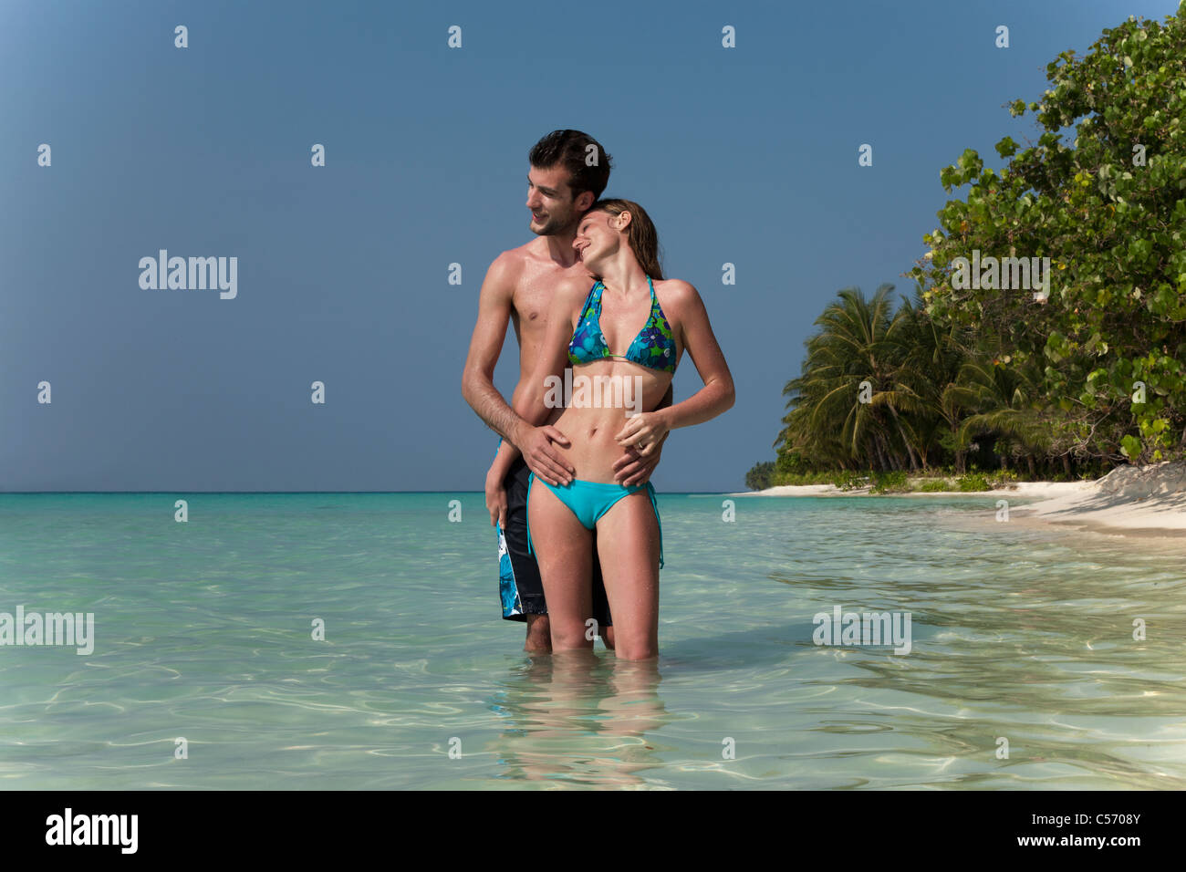 Couple hugging in water on beach Stock Photo