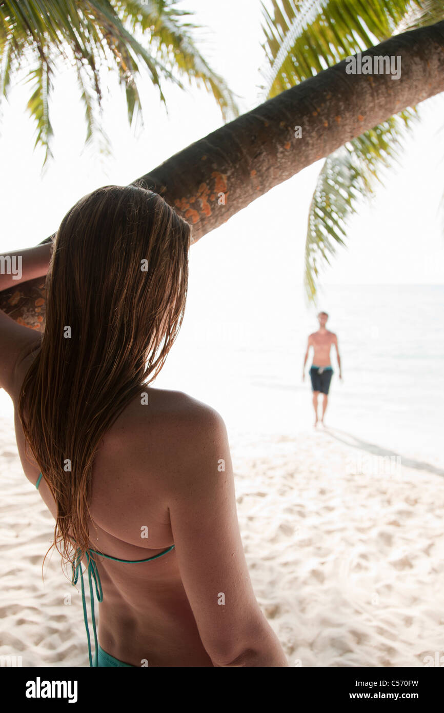 Woman admiring man on tropical beach - Stock Image