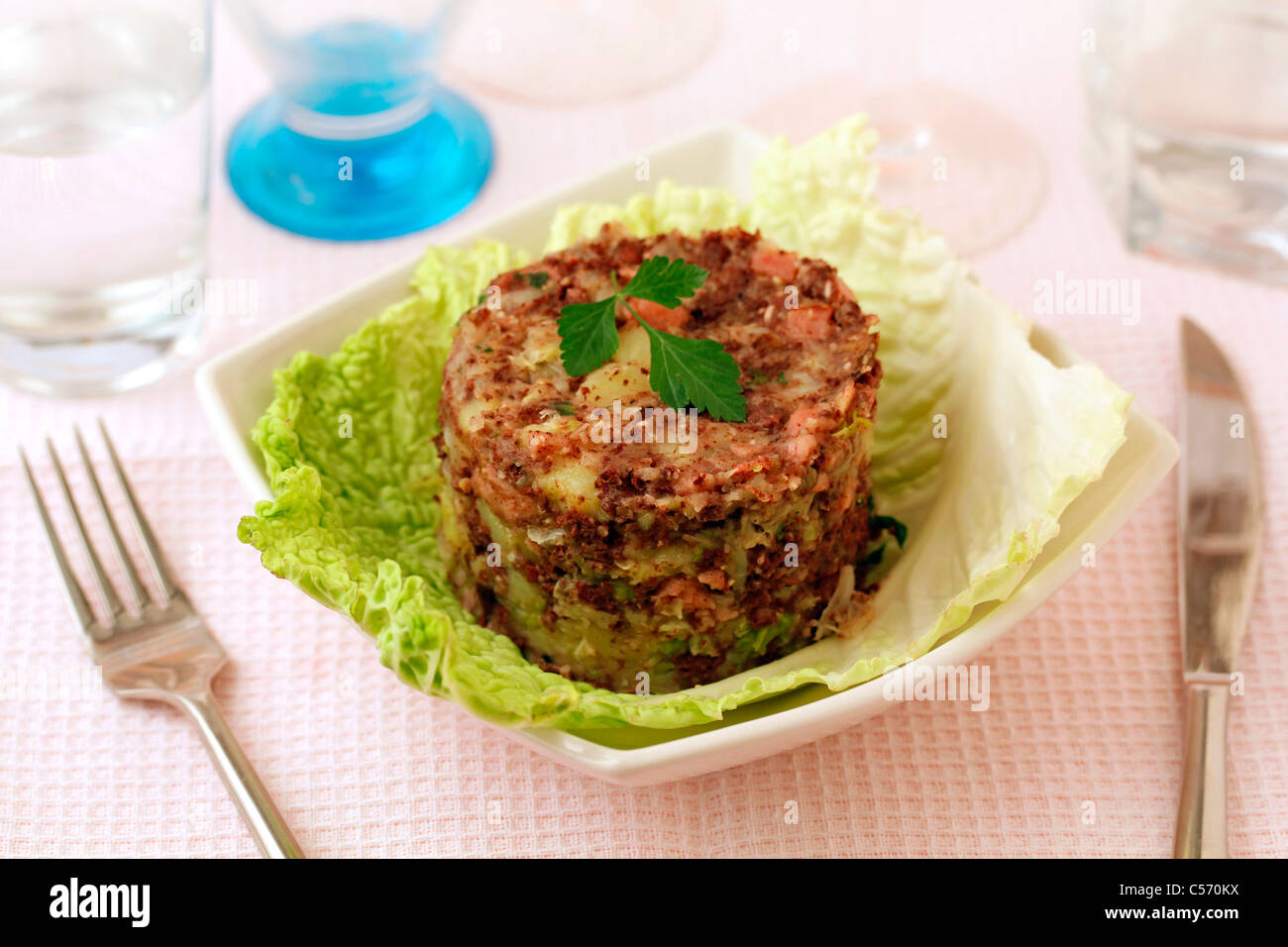 Mashed cabbage and potatoes fried with black sausage. Recipe available. Stock Photo