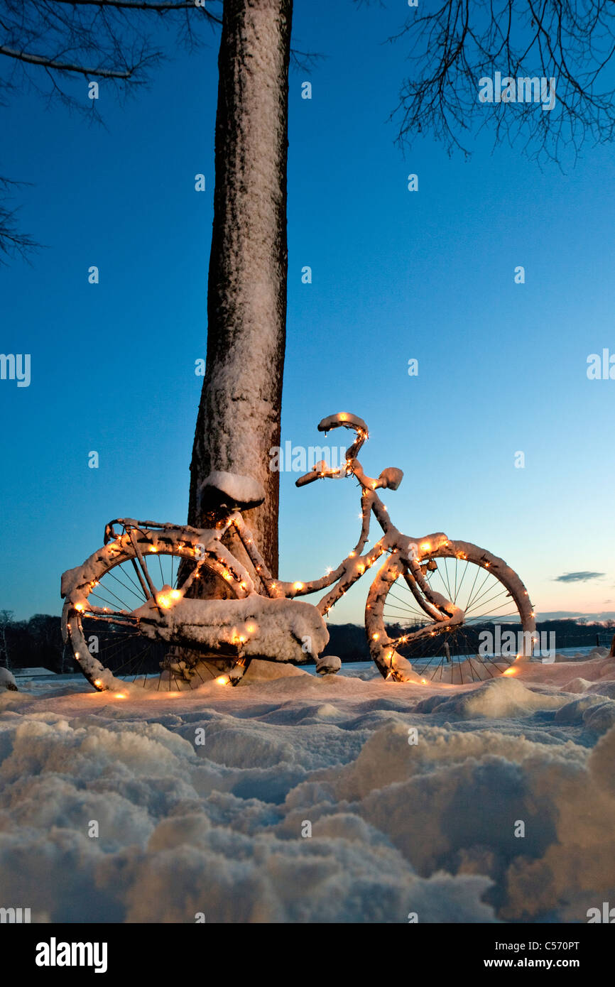 The Netherlands, 's-Graveland, bicycle decorated with Christmas lights in snow. Dawn. - Stock Image