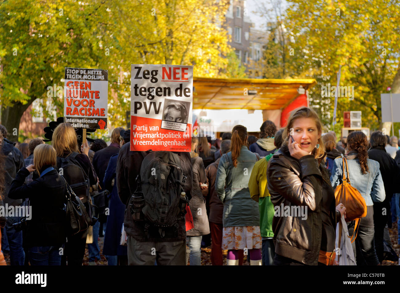 Girl makes a phone call during an anti-racism demonstration in Amsterdam watched by eyes in placard - Stock Image
