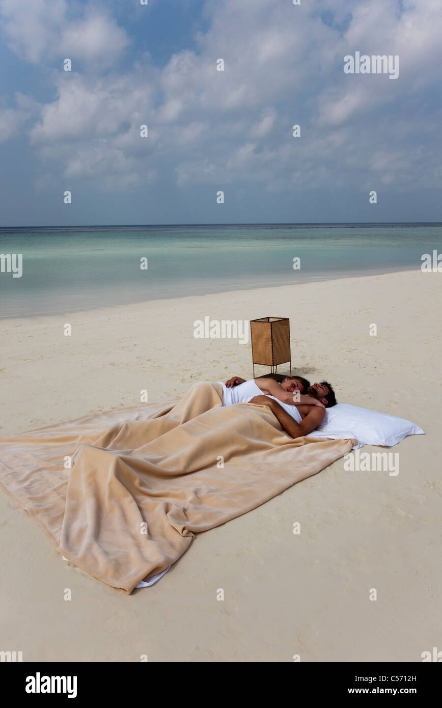Couple sleeping in bed on beach - Stock Image