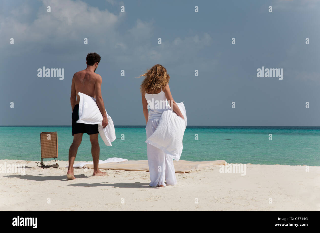 Couple making bed on tropical beach - Stock Image