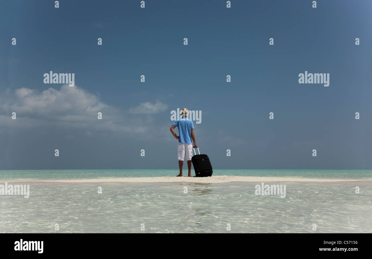 Lost man with luggage on beach - Stock Image