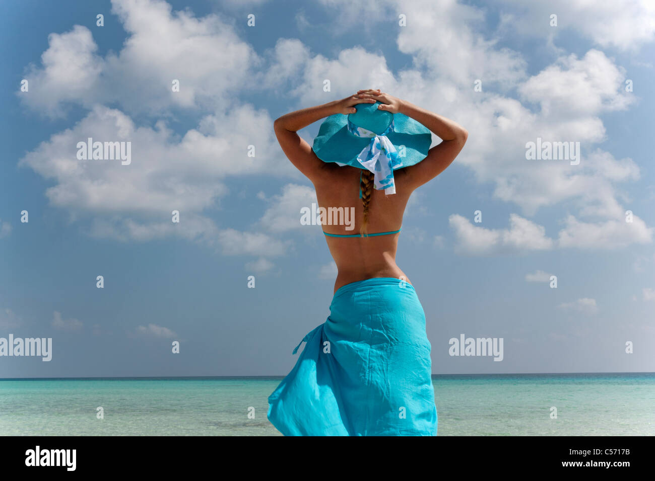 Woman standing on tropical beach - Stock Image