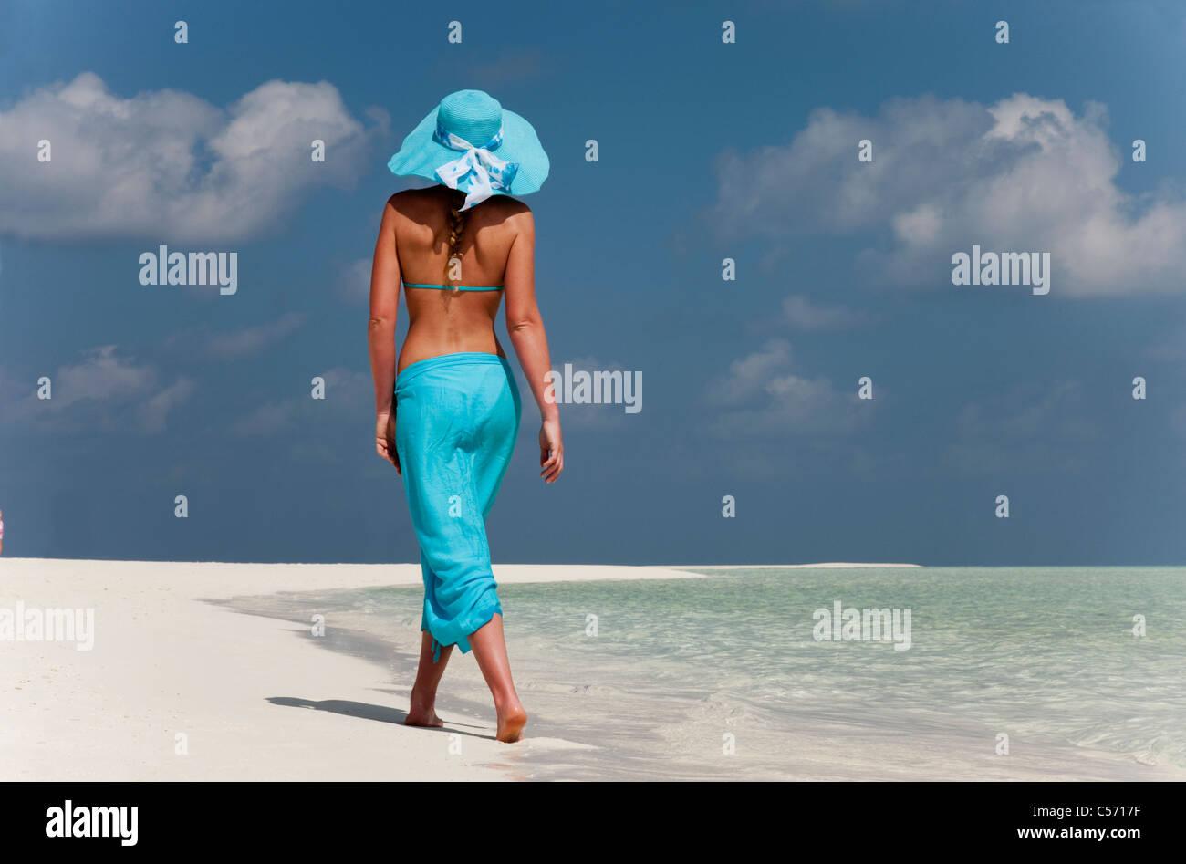 Woman walking on tropical beach - Stock Image