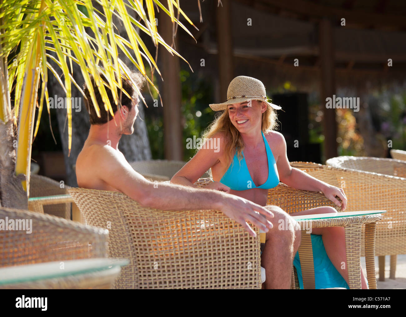 Couple sitting in wicker chairs outdoors - Stock Image