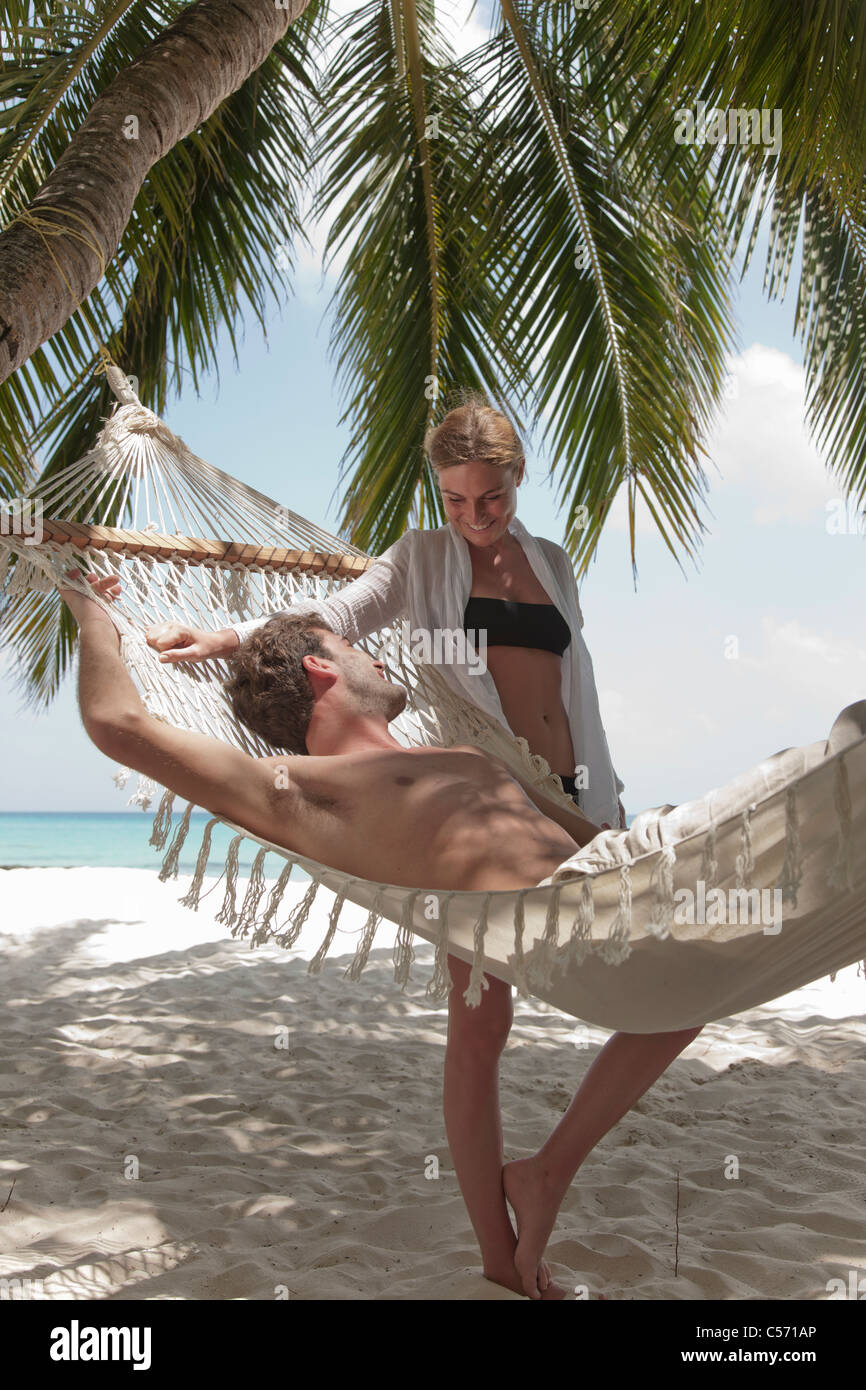 Couple relaxing with hammock on beach - Stock Image