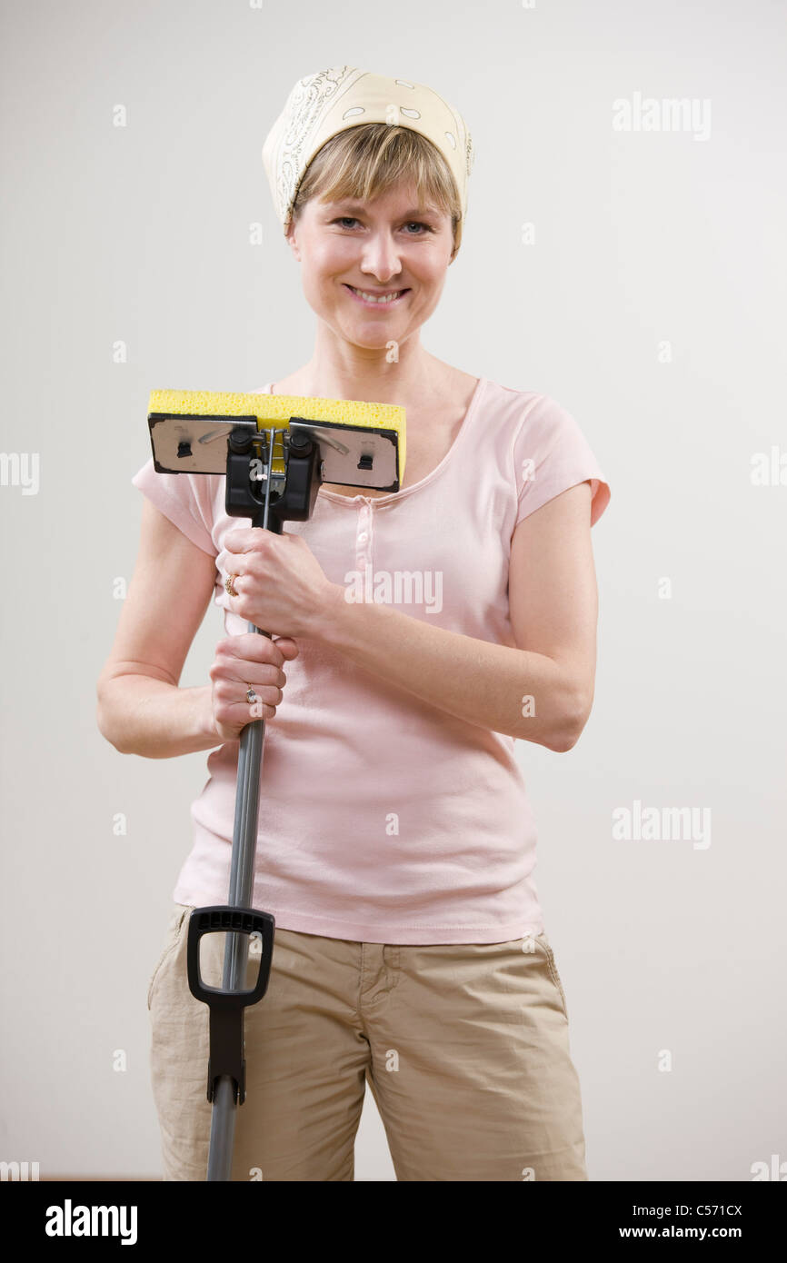 Smiling woman holding mop - Stock Image
